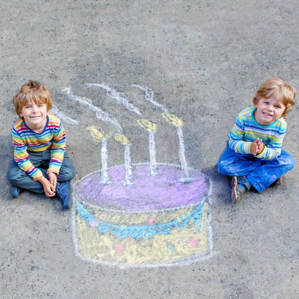 zwei jungs, die spaß mit bunten geburtstagstorte zeichnen mit kind - vorschulgeburtstag stock-fotos und bilder