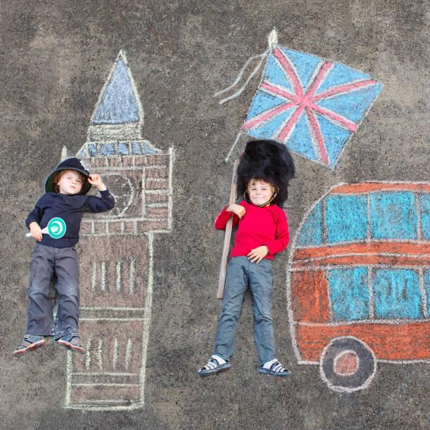 zwei jungs in uniform mit london pi britischer soldat polizist kid - lustige babybilder stock-fotos und bilder