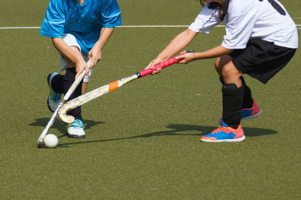 Two kid field hockey players compet stock photo