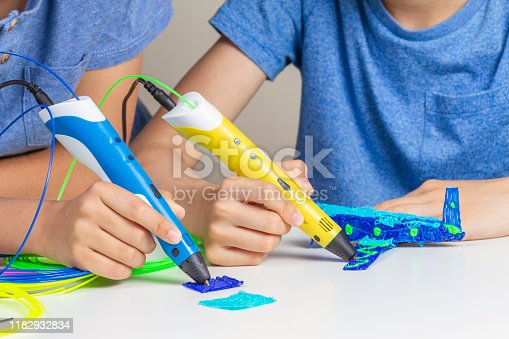 899701486 istock photo Two kid hands creating with 3d printing pens 1182932834