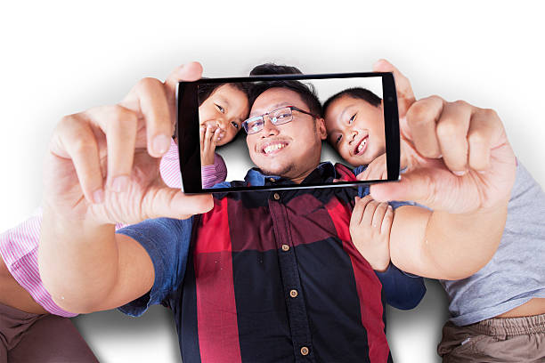 Two kids and father taking selfie together stock photo