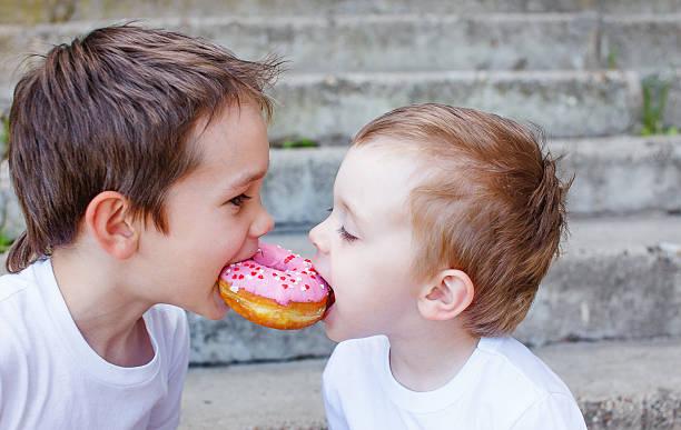 two kids bite off a donut and having fun - foto de stock