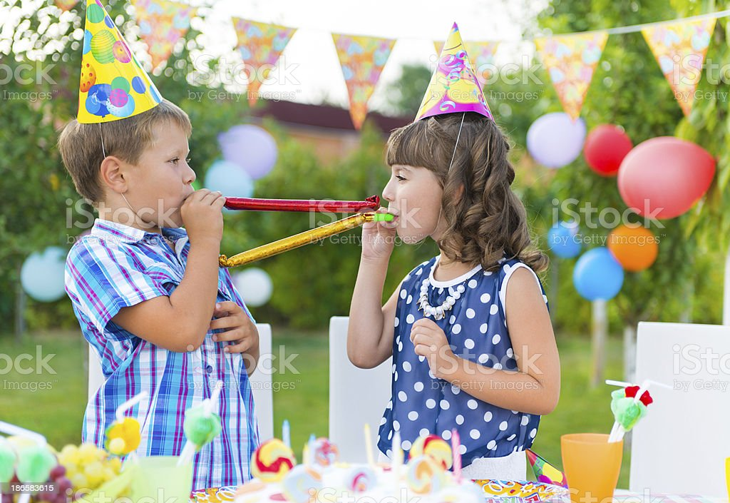 Two kids blowing party favors at an outdoor birthday party royalty-free stock photo
