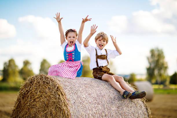 zwei kinder, jungen und mädchen in bayerischer tracht im weizenfeld mit heuballen - bayerische tracht stock-fotos und bilder