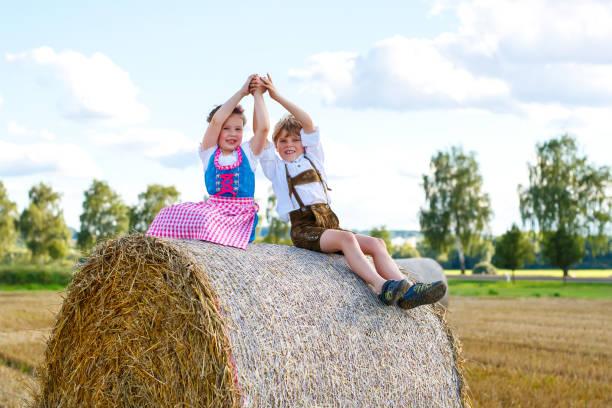 zwei kinder, jungen und mädchen in bayerischer tracht im weizenfeld mit heuballen - sommerfest kindergarten stock-fotos und bilder