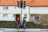 Two active kids boys in helmet biking on bicycles in the city. Happy children in colorful clothes and waiting for green traffic light. Safety and protection for preschool kids.
