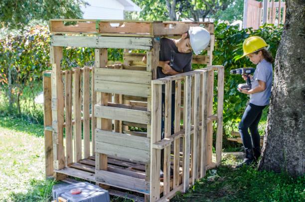 Zwei Kinder bauen eine Holzhütte – Foto