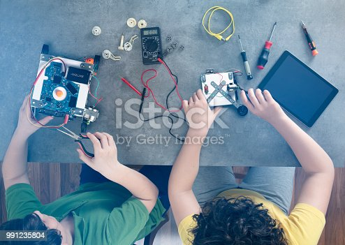 865186916 istock photo Two kids builds a robot. 991235804