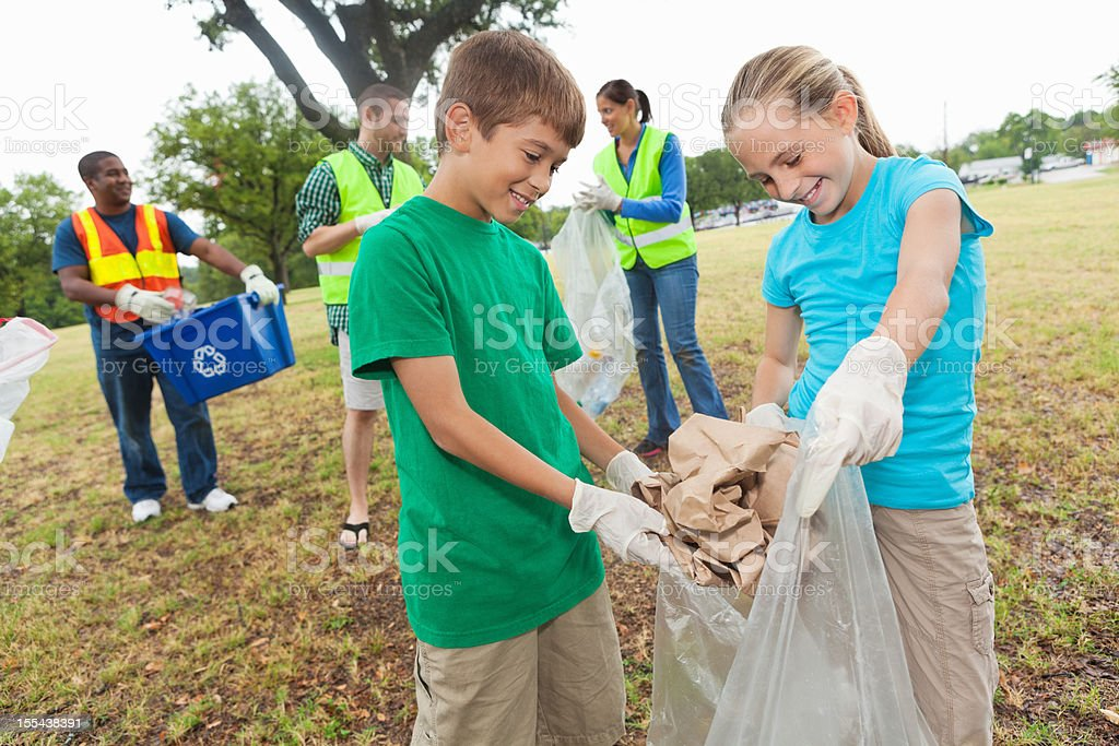 Two kids collecting and throwing away garbage with volunteer team royalty-free stock photo