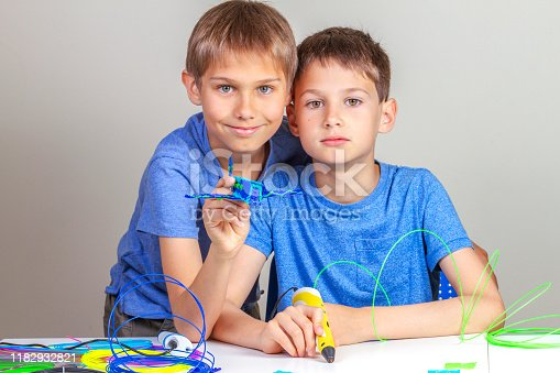 899701486 istock photo Two kids creating with 3d printing pens 1182932821