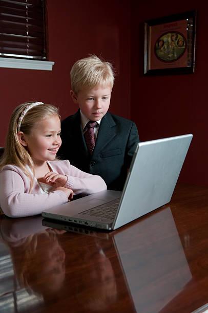 zwei kinder gekleidet in abendgarderobe blick auf laptop - mark tantrum stock-fotos und bilder