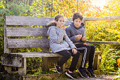 Girl and boy eating apple and orange while sitting on a bench in the forest during a day of autumn