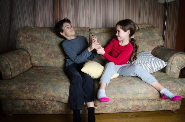 Zwei Kinder kämpfen für die TV-Fernbedienung beim Sitzen auf der Couch im Wohnzimmer – Foto