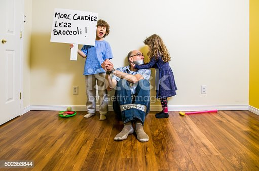 A father has his legs and hands attached with duct tape and sits on the floor while his daughter is putting tape on his mouth and his son is showing a placard with their demands: more candies, less broccoli