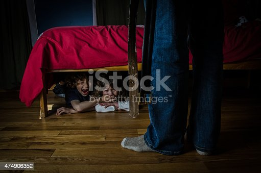 Two kids (brother and sister) are hiding under the bed with fear and the brother is muting her sister with his hand and while the father is in front of the bed with his belt hanging besides him