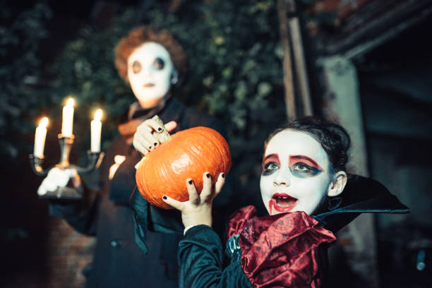 two kids in spooky halloween costumes with candleholder and pumpkin stock photo