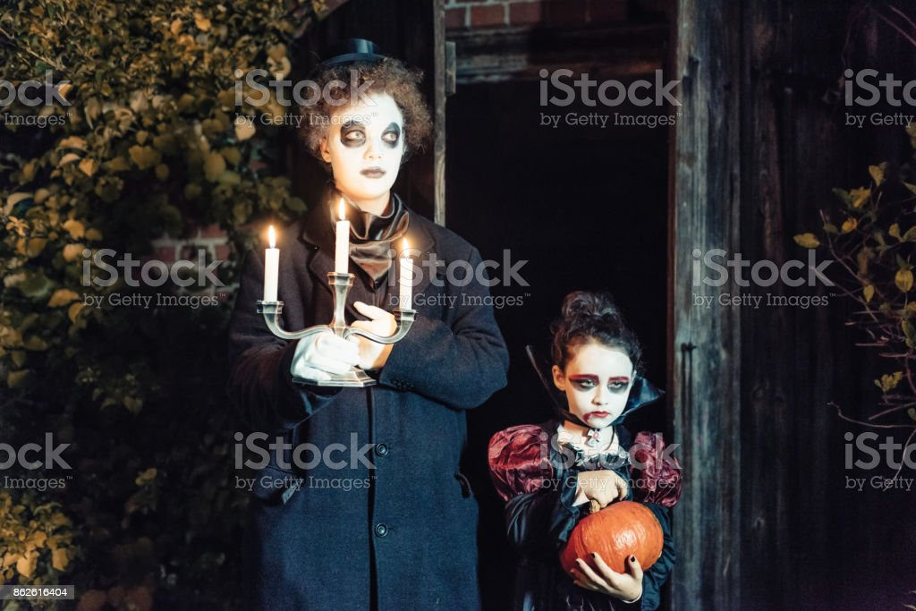 two kids in spooky halloween costumes with candleholder royalty free stock photo