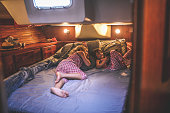 Two little girls relax on the bed of a live aboard sailboard head berth, cheerful and relaxed they are content watching a tablet together in the cabin of a large luxury boat