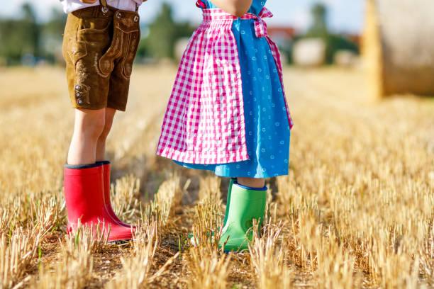 zwei kinder in bayerischer tracht und rote und grüne gummi-stiefel im weizenfeld - sommerfest kindergarten stock-fotos und bilder