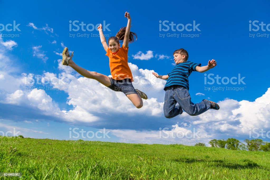 Two kids jumping on green hills stock photo