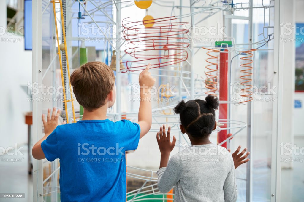 Two kids looking at a science exhibit,  back view stock photo