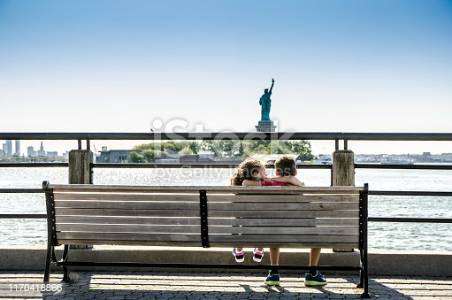 585604690istockphoto Two kids looking at Statue of Liberty 1170418866