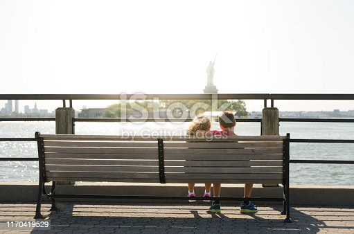 Two kids looking at Statue of Liberty from the Liberty State Park in Jersey city during summer day