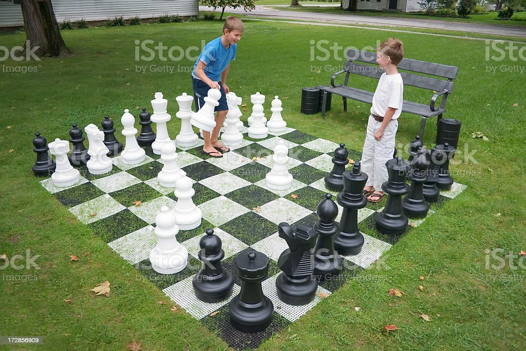 Two kids playing a chess game with large pieces on grass stock photo