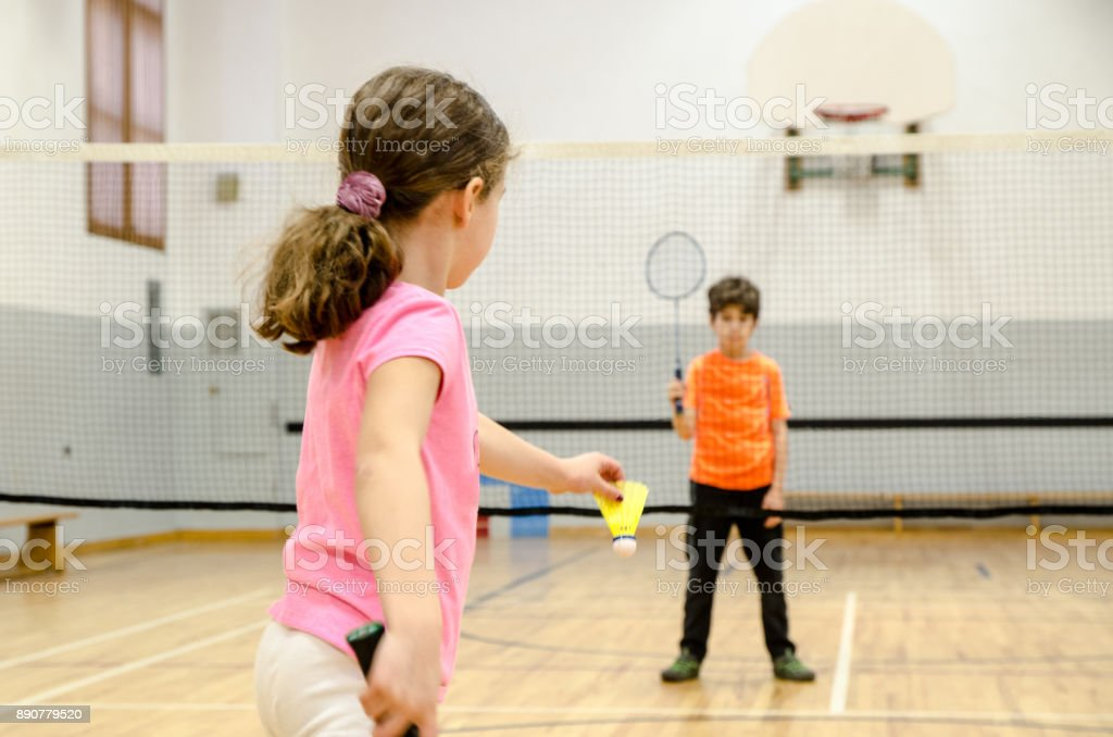 Two kids playing badminton in a gymnasium – zdjęcie