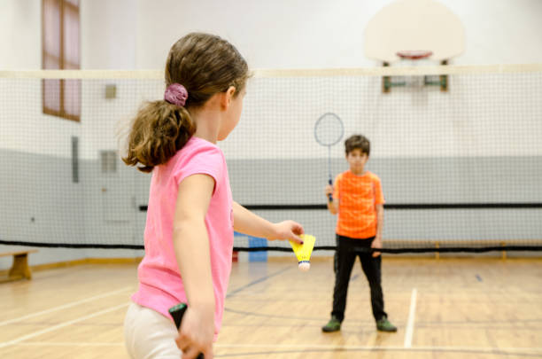 Two kids playing badminton in a gymnasium Two kids playing badminton in a gymnasium   badminton stock pictures, royalty-free photos & images