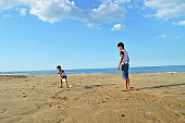 Two kids playing cricket on a beach by the sea on a summer day.