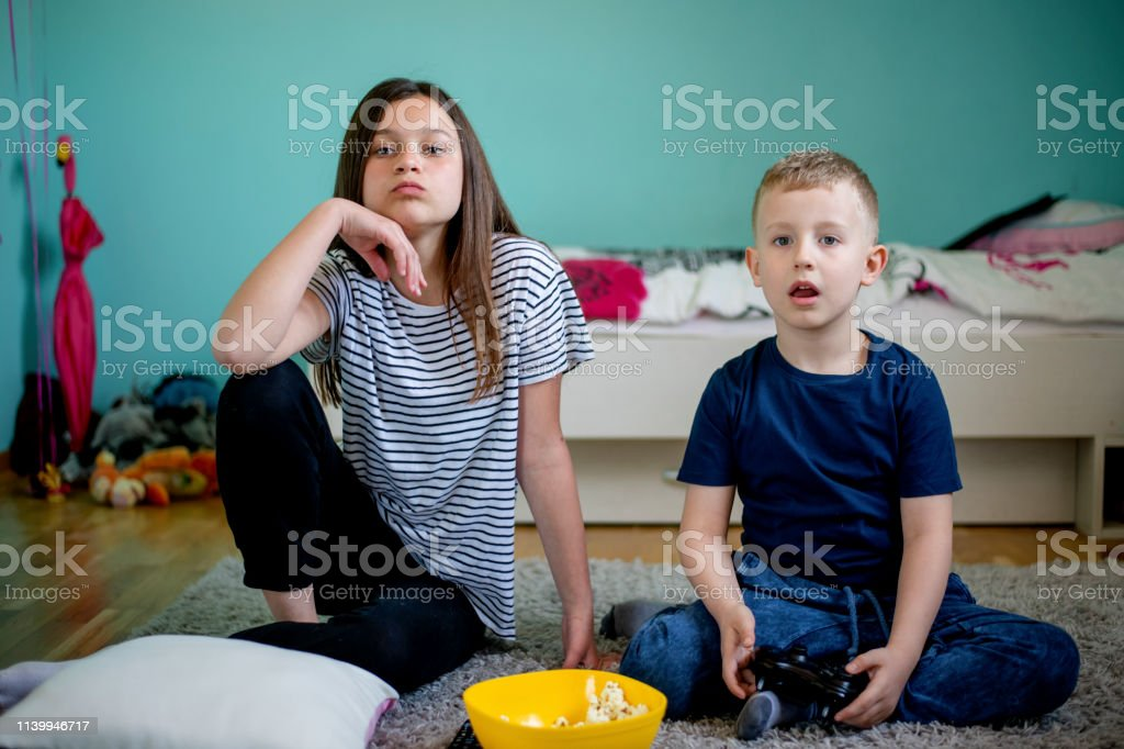 Two kids playing game console. Brother and older sister playing video...