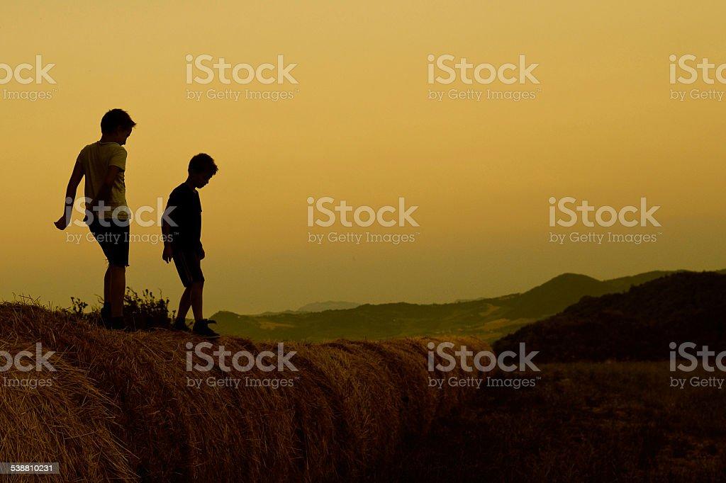 Zwei Kinder spielen im Heu bales bei Sonnenuntergang – Foto