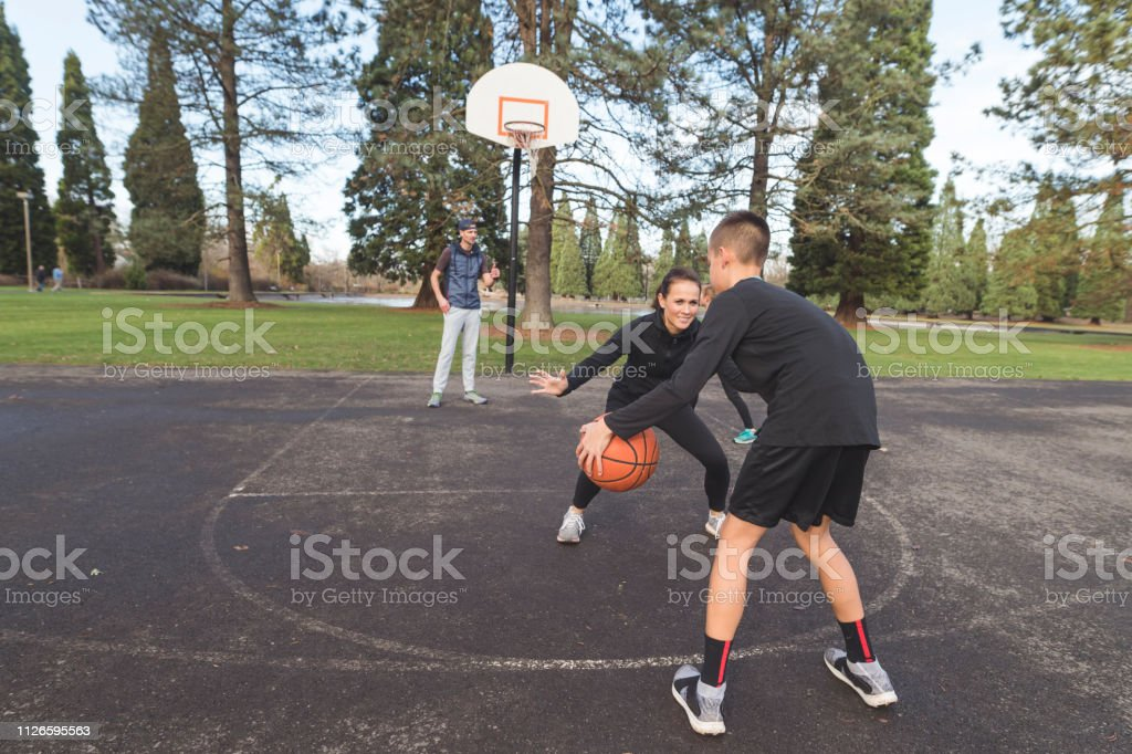 An elementary-age boy dribbles a basketball and tries to score on his...