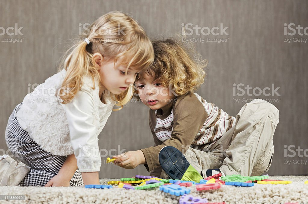 Two kids playing together with puzzles. royalty-free stock photo
