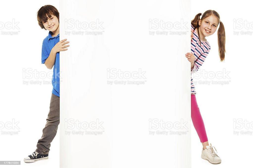 Duas crianças mostrando nova publicidade em branco. - foto de acervo