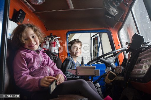 Two kids (boy and girl) sit in a firetruck with big smile
