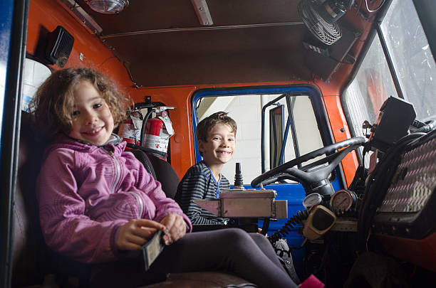Two kids sit in firetruck with big smile