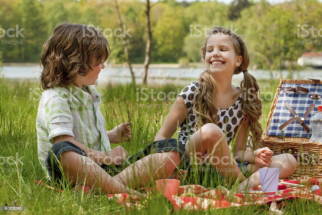 Two kids smiling while picknicking stock photo