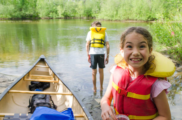 Two kids, standing in river water, besides canoe
