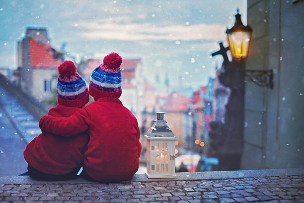 two kids, standing on a stairs, holding a lantern - christmas tree stockfoto's en -beelden