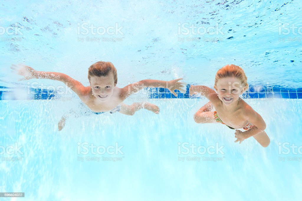 two kids swimming underwater in a pool royalty free stock photo - Kids Swimming Underwater