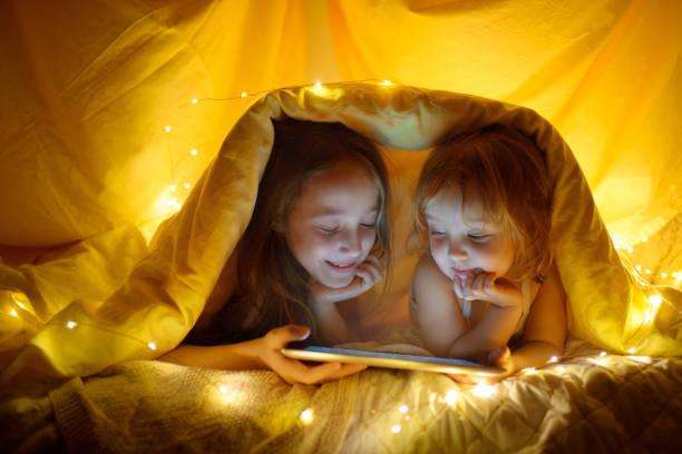 zwei kinder mit tablet-pc unter decke in der nacht. - deckenleuchte kinderzimmer stock-fotos und bilder