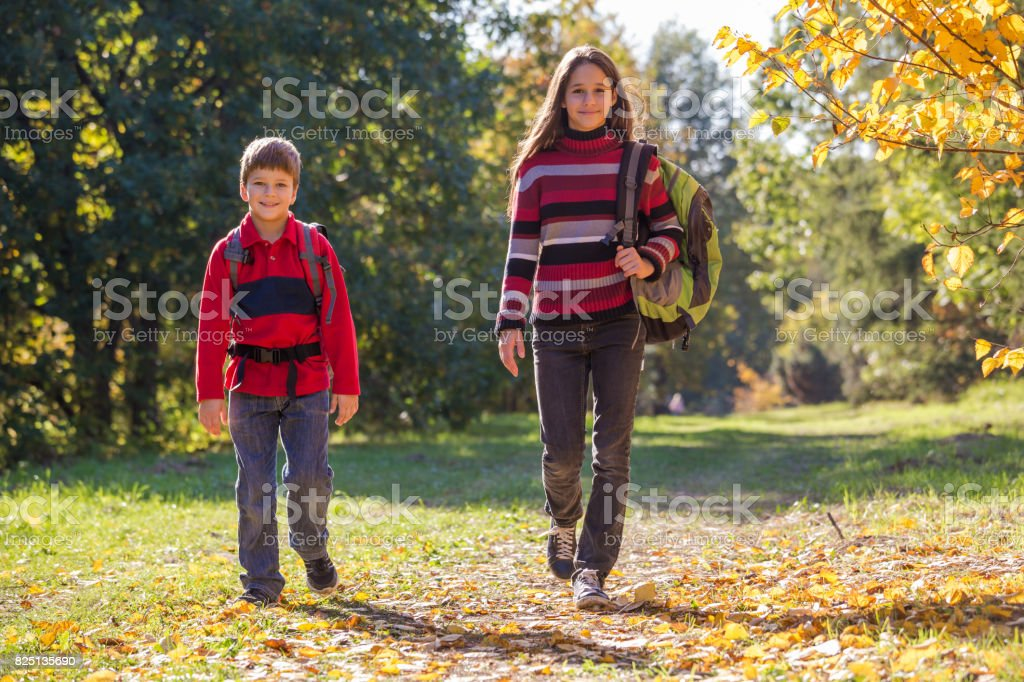 Two Kids Walk Around On Autumn Forest With Backpacks Stock Photo