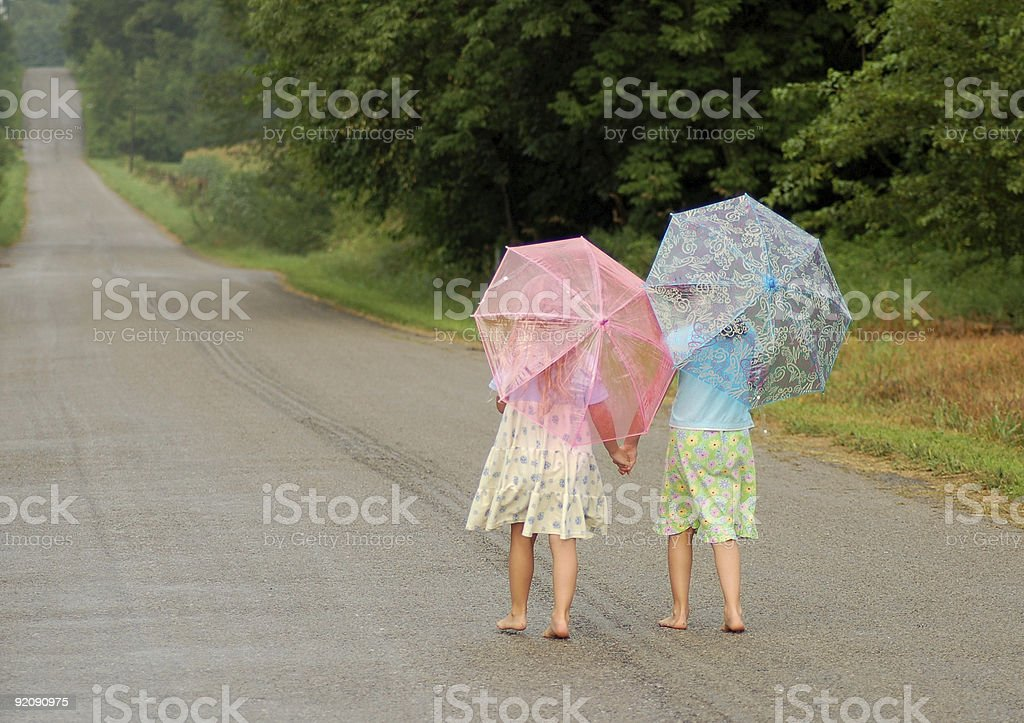 Two kids Walking Together Hand-in-Hand With Umbrellas stock photo