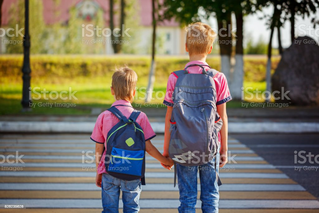 Two Kids With Backpacks Walking On The Road Holding School Tim Stock