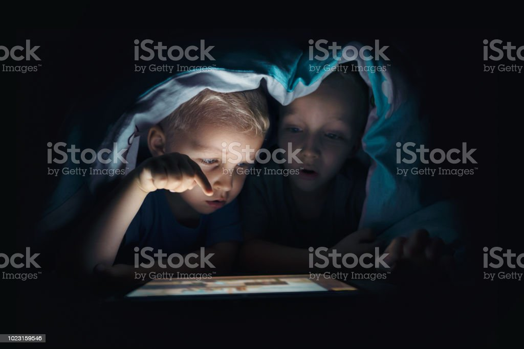 Two kids with tablet computer in a dark room stock photo