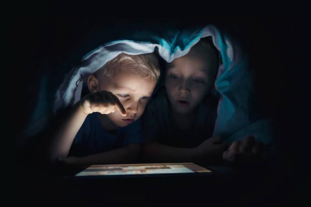zwei kinder mit tablet-pc in einem dunklen raum - online spiele spielen stock-fotos und bilder