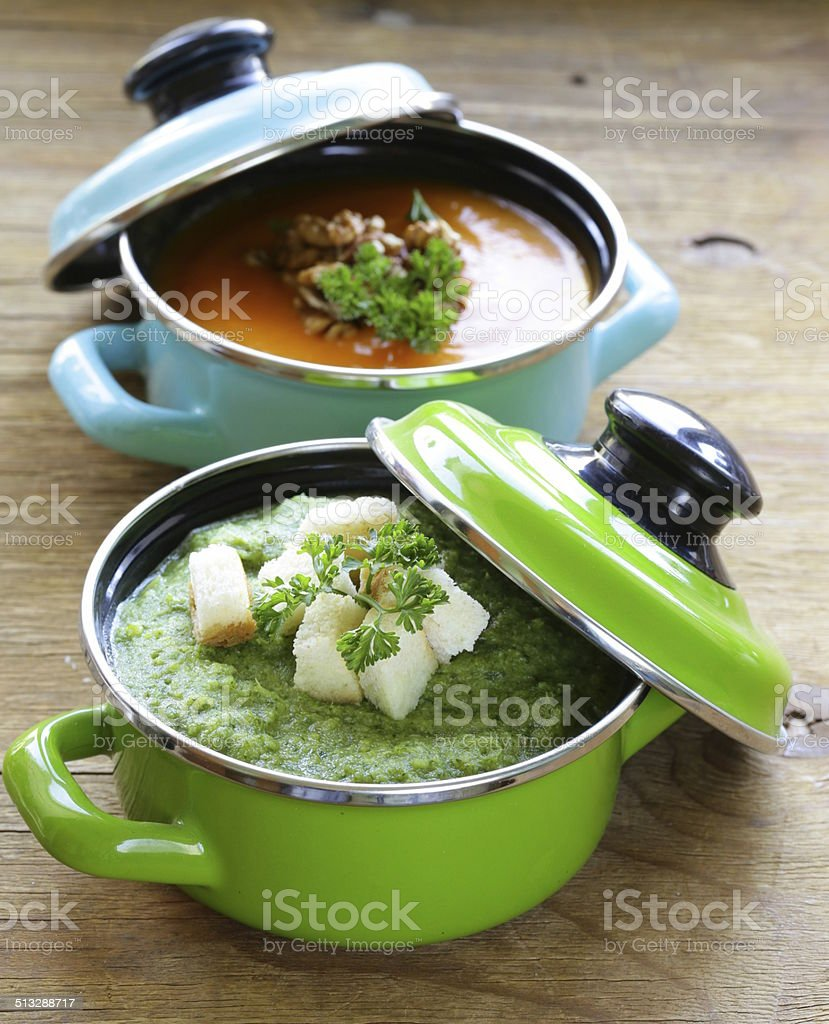 two kinds of cream soup (broccoli and pumpkin) in pot stock photo