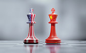 Two king chess pieces textured with American and Chinese flags on black and white chessboard. Politics and checkmate concept. Horizontal composition with selective focus and copy space.
